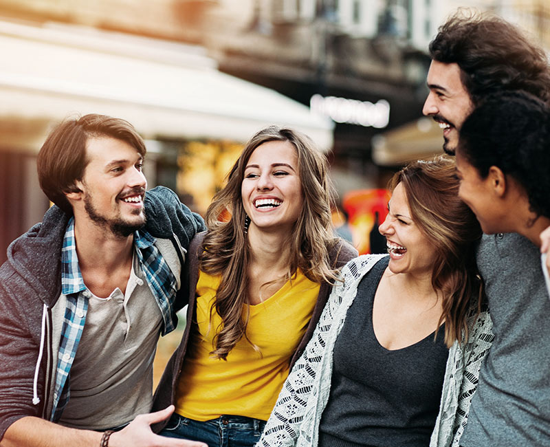 Group of young adults walking down the street laughing
