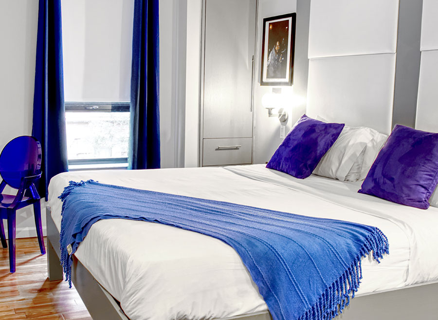 king room with large bed and purple pillows