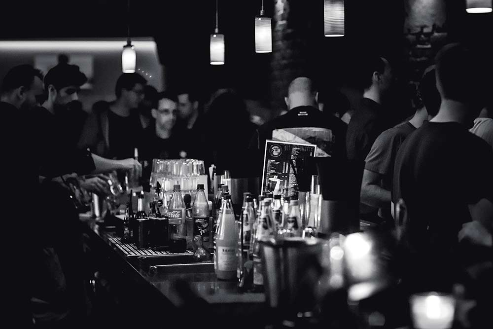 Patrons crowding around a lively bar