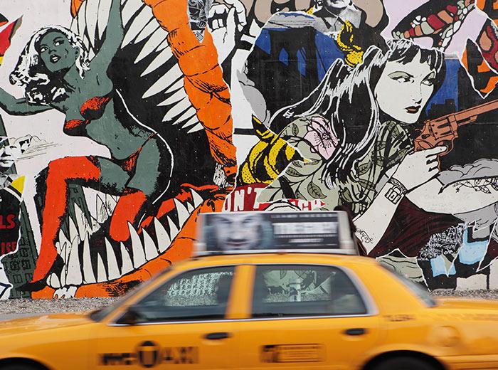 A taxi driving past wall graffiti