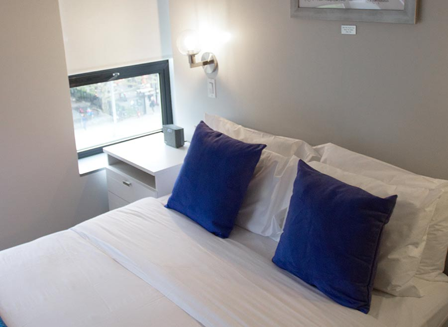 room with queen bed, window and mounted tv