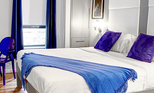 A hotel room with bright blue pillows