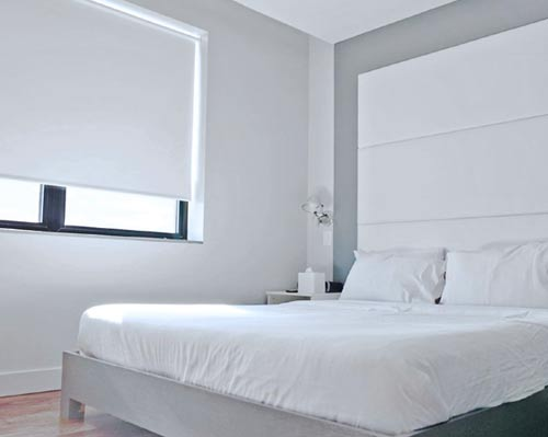 A bed with white sheets and white zig zag pillows