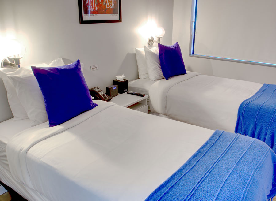 two twin beds side by side with purple pillows